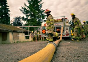 yellow hose in foreground with firefighter carrying ladder